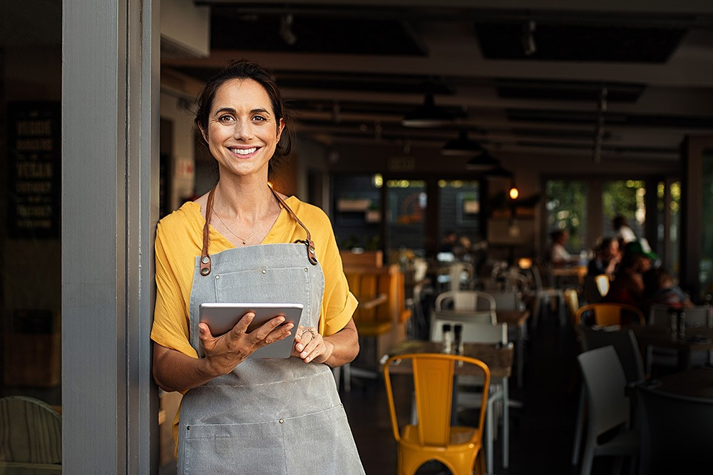 A woman in front of her restaurant committing to the highest standards of people assurance and safety for her guests and employees.